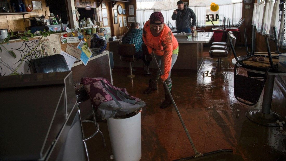 Tina Dry mops up water and mud that seeped into her family's diner, Kim's Country Cafe, after area storms brought flood-level water to the Colusa County town of Maxwell on February 18.