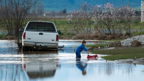Barr Torrens plays in flooded neighborhood streets after a deluge of rain and water-runoff flooded much of Maxwell, California, February 18.