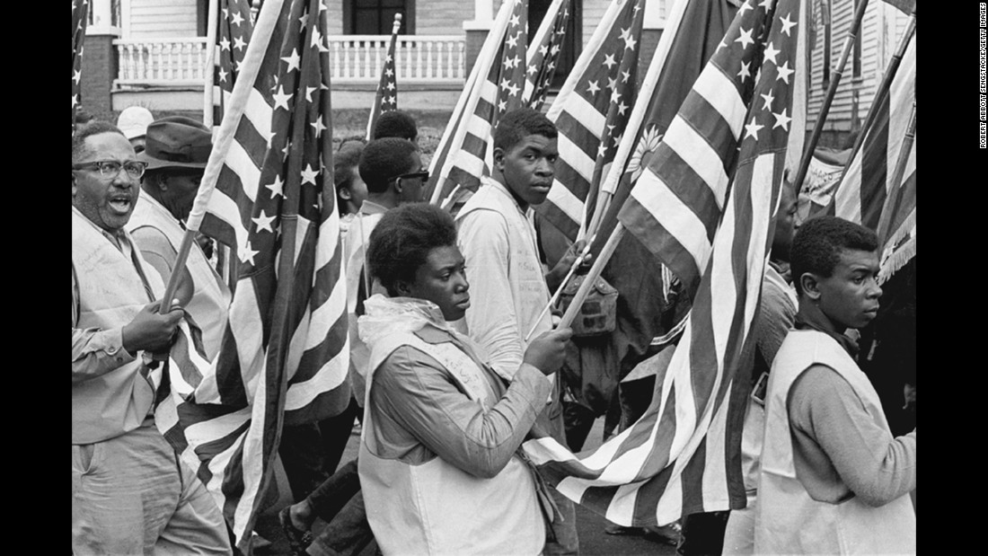Protesters carry American flags during their march to Montgomery.