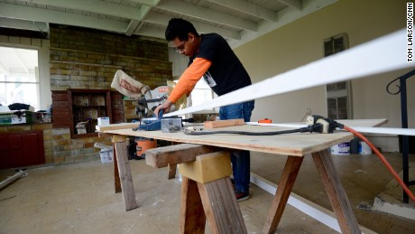 Workers rush to finish flooring for homes meant to hide immigrants.