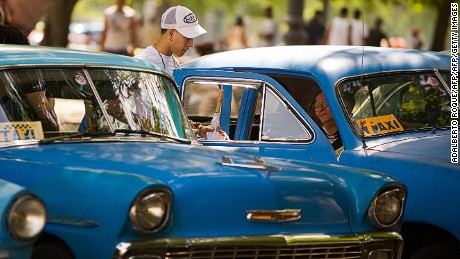 Passengers get into a taxi in Havana, on September 11, 2009. The Cuban government began to assign permits to use private cars as taxis and for cargo, in order to mitigate the effects of the crisis in the sector.  AFP PHOTO/ADALBERTO ROQUE (Photo credit should read ADALBERTO ROQUE/AFP/Getty Images)