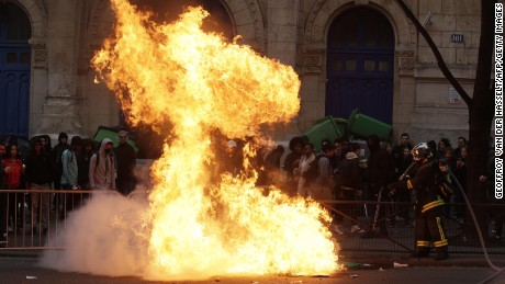 Firemen try to extinguish burning dustbins at Paris protest.