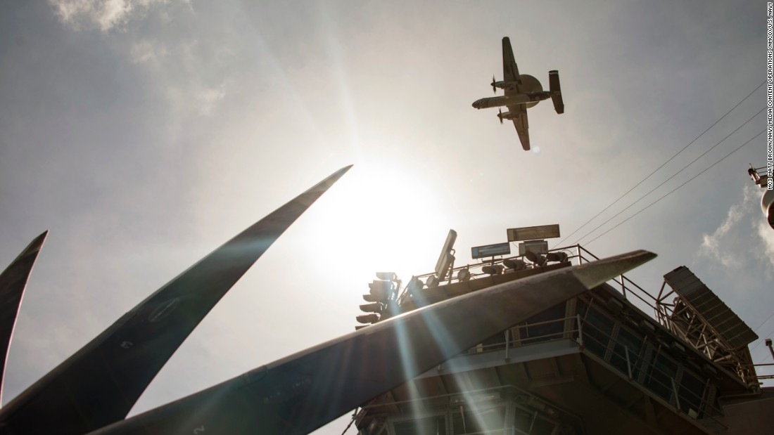 An E-2C Hawkeye early warning and control aircraft flies over the aircraft carrier USS Carl Vinson on February 23.