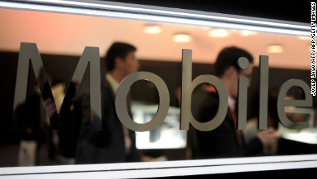 "Visitors use their mobile phone as they are reflected in a mirror with the word ""Mobile"" on it during the opening day of the 2015 Mobile World Congress (MWC) in Barcelona on March 2, 2015. Phone makers will seek to seduce new buyers with even smarter Internet-connected watches and other wireless gadgets as they wrestle for dominance at the world's biggest mobile fair starting today. AFP PHOTO / JOSEP LAGO        (Photo credit should read JOSEP LAGO/AFP/Getty Images)"
