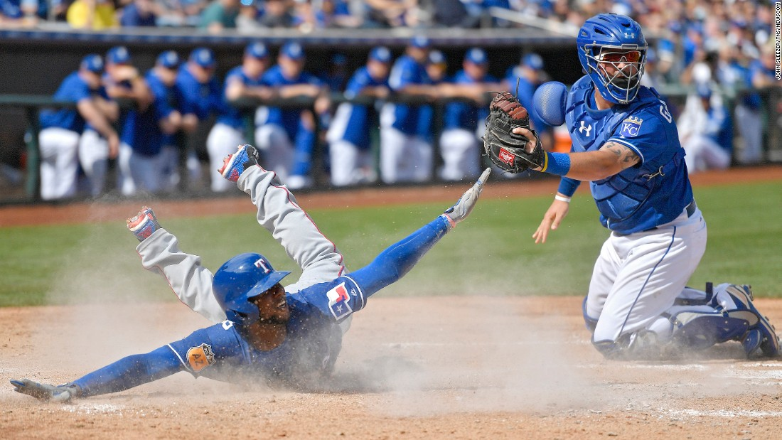 Texas' Jurickson Profar slides past Kansas City catcher Cam Gallagher during a spring-training game in Surprise, Arizona, on Sunday, February 26.