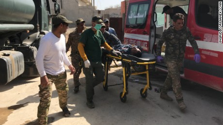 An injured soldier is rushed into the clinic from an ambulance.