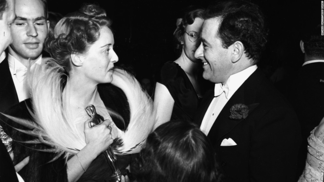 "Davis chats with her favorite director, William Wyler, after winning her second Oscar. She took home the prize as a Southern belle in Wyler's ""Jezebel"" (1938), consolation for losing the role of Scarlett O'Hara in ""Gone With the Wind."" Wyler also directed her in ""The Letter"" (1940) and ""The Little Foxes"" (1941). ""I would have jumped into the Hudson River if this man had told me to, directorially speaking,"" Davis said in her 1962 autobiography, ""The Lonely Life."""