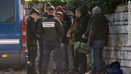 French police examine the identity documents of migrants in Calais.