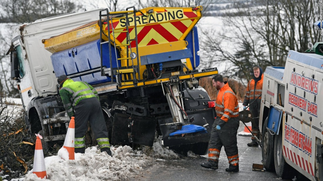 Workers recover an overturned salt truck in Balfron, Scotland, on Thursday, February 23.