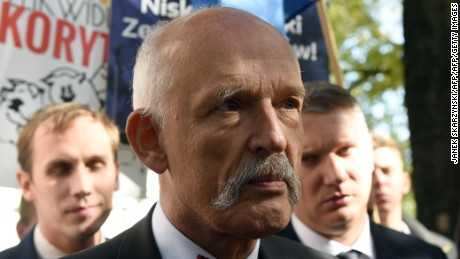 Polish right-wing politician and European Parliament member Janusz Korwin-Mikke talks to reporters in front of the Polish parliament building in Warsaw on Thursday, October 8, 2015. Right-wing politician and European Parliament member Janusz Korwin-Mikke brought four pigs to protest against the country's main political parties, which he compares to well-fed pigs. His small party is not expected to win any seats in the October 25 general election. AFP PHOTO / JANEK SKARZYNSKI        (Photo credit should read JANEK SKARZYNSKI/AFP/Getty Images)