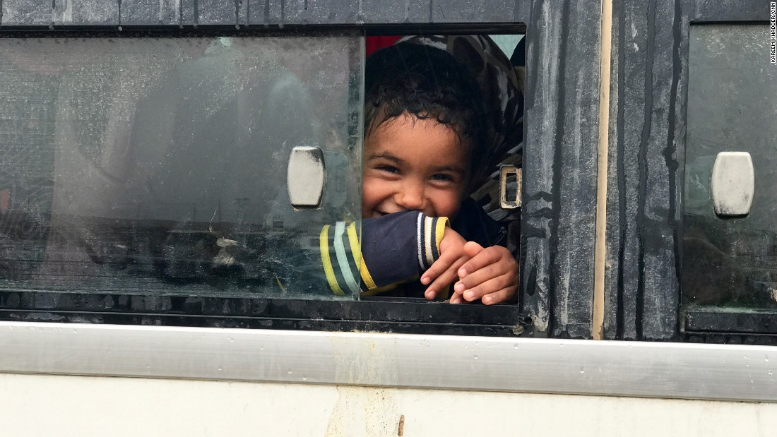 A young Iraqi boy smiles as he sits on a bus before being transported with his mother and other civilians fleeing western Mosul to a nearby refugee camp.