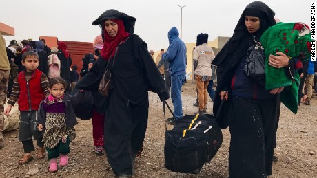 Two Iraqi Women with their children and few possessions they could gather before escaping the city arrive to an internally displaced reception point area south of Mosul. Women living under ISIS rule were ordered to cover their faces and bodies with veils and black dresses. who did not follow order were punished by lashing or other means. Women CNN spoke to south of Mosul were happy to flee western Mosul and ISIS rule. Women are seen removing the veils of their faces.