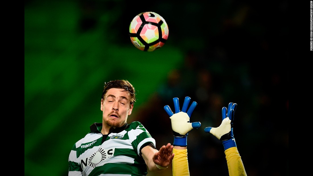 A goalkeeper reaches for the ball as Sporting Lisbon defender Sebastian Coates heads it during a match in Portugal on Sunday, March 5.