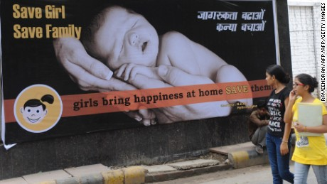 Women walk past a billboard in New Delhi in 2010. India has long struggled with sex-selective abortions, leading to a growing gender gap.