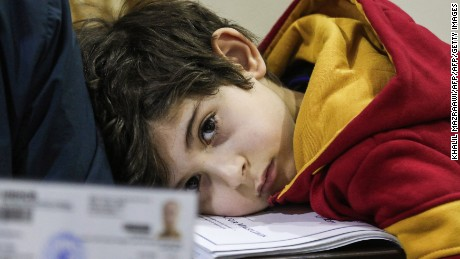 Ward Faraj al-Jamous, a child Syrian refugee, rests his head on a stack of documents as his father gives an interview, after his family was prevented from travel to the United States when President Donald Trump's executive order blocking entry to citizens from seven Muslim-majority countries, including Syria, was enacted without warning, in the Jordanian capital Amman on February 1, 2017. After spending over a year amid interviews, health and security checks, the Jamous family of seven was contacted by a representative from the International Organisation of Migration (IOM) who told him that the family's immigration and resettlement plans were suspended indefinitely. / AFP / Khalil MAZRAAWI        (Photo credit should read KHALIL MAZRAAWI/AFP/Getty Images)