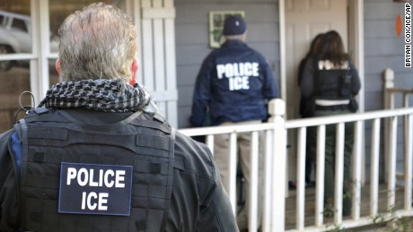 ICE agents stand outside an Atlanta home during a February operation.
