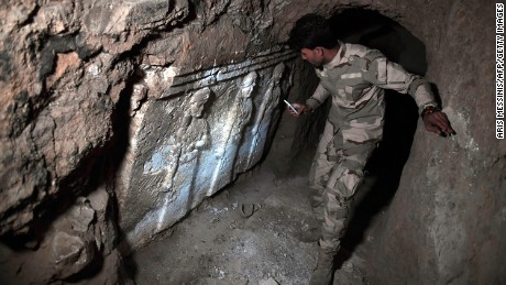 An Iraqi troop member examines ancient artifacts found in an underground ISIS tunnel in eastern Mosul.