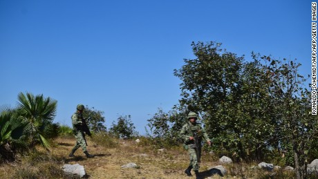 Mexican soldiers search for corpses in the surroundings of a mass grave, in the Zitlala municipality, Guerrero State, Mexico on November 25, 2016.  Authorities have exhumed 32 bodies and nine heads from several clandestine graves in a southern Mexican state plagued by kidnappings, murders and drug cartel turf wars, officials said Thursday. The remains were unearthed between Tuesday and Thursday in 17 pits on a hill in the village of Pochahuixco, part of the municipality of Zitlala. / AFP / RONALDO SCHEMIDT        (Photo credit should read RONALDO SCHEMIDT/AFP/Getty Images)