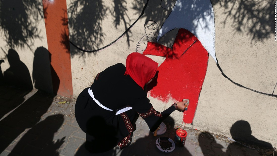 A Palestinian artist applies the final touches to a street mural in Gaza City.