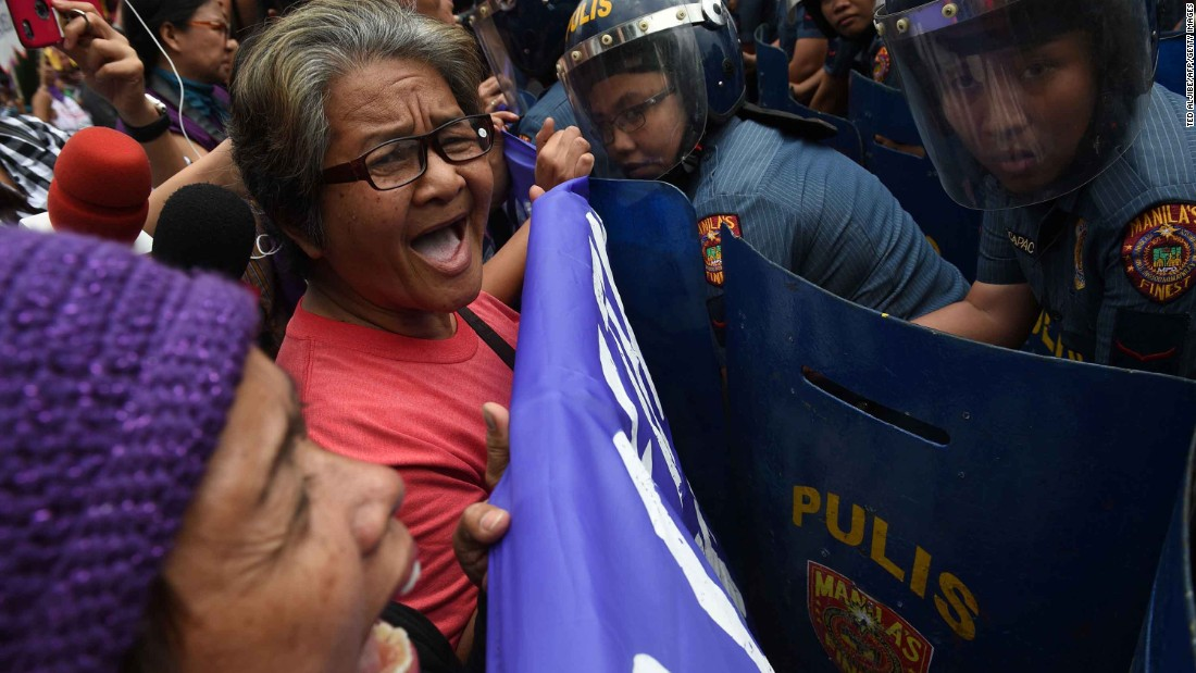 Members of a women's group face off against female police officers as they shout anti-American slogans near the US Embassy in Manila, Philippines. Many protesters this year have turned out to voice their disagreement with the policies and rhetoric of US President Donald Trump, especially regarding women's issues.
