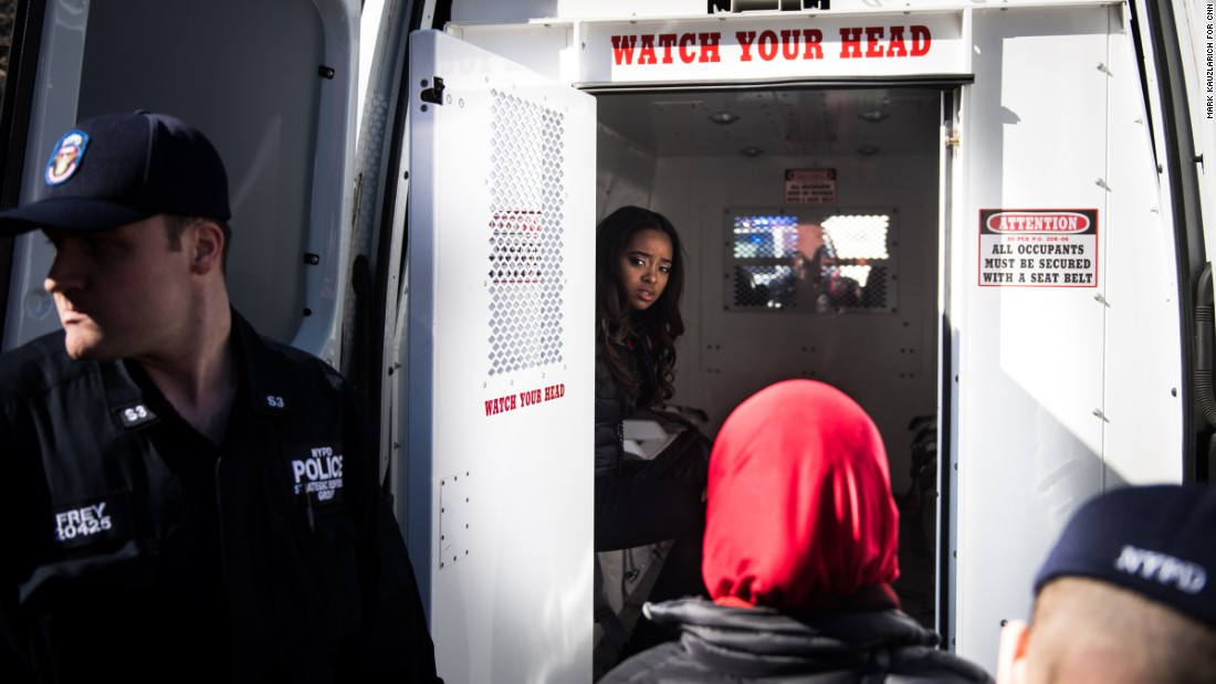 "Activist Tamika Mallory sits in the back of a police van after being detained for blocking traffic outside the Trump International Hotel and Tower in New York. ""Many of our national organizers have been arrested in an act of civil disobedience,"" <a href=""https://twitter.com/womensmarch/status/839558787753263104"" target=""_blank"">tweeted the Women's March organization.</a> ""We will not be silent."""