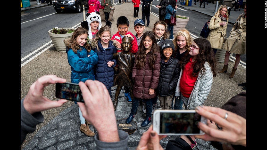 "Children crowd around the ""Fearless Girl"" statue for a group photo. She <a href=""http://money.cnn.com/2017/03/08/news/wall-street-fearless-girl-reaction/"">has become the most popular girl on Wall Street</a>, and some fans are pushing for the statue to remain a permanent fixture."