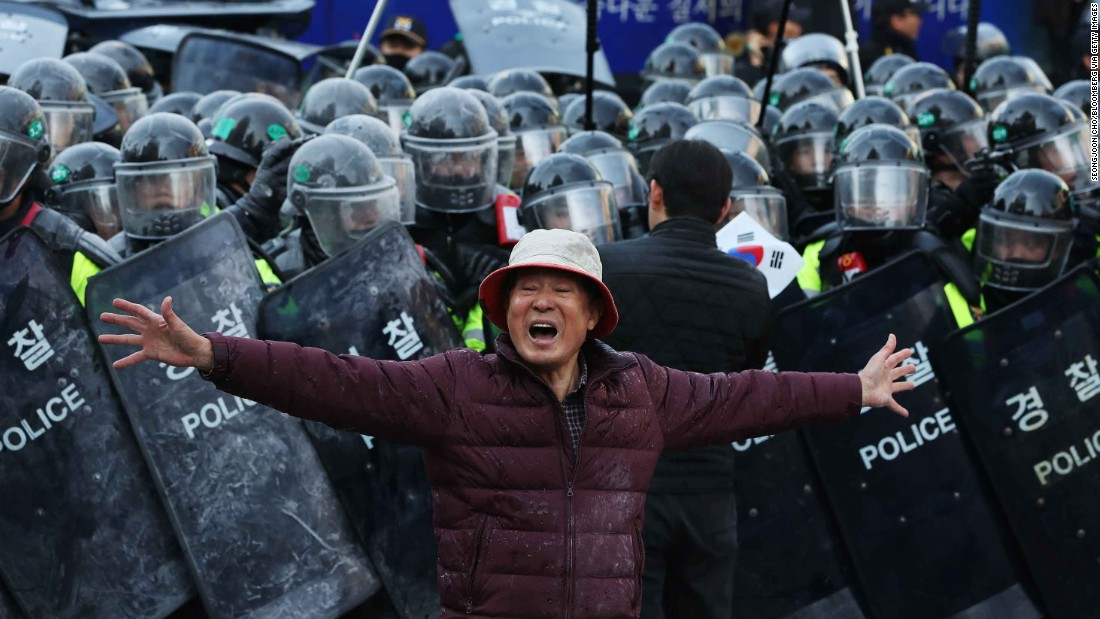 A Park supporter shouts slogans in front of a police line.