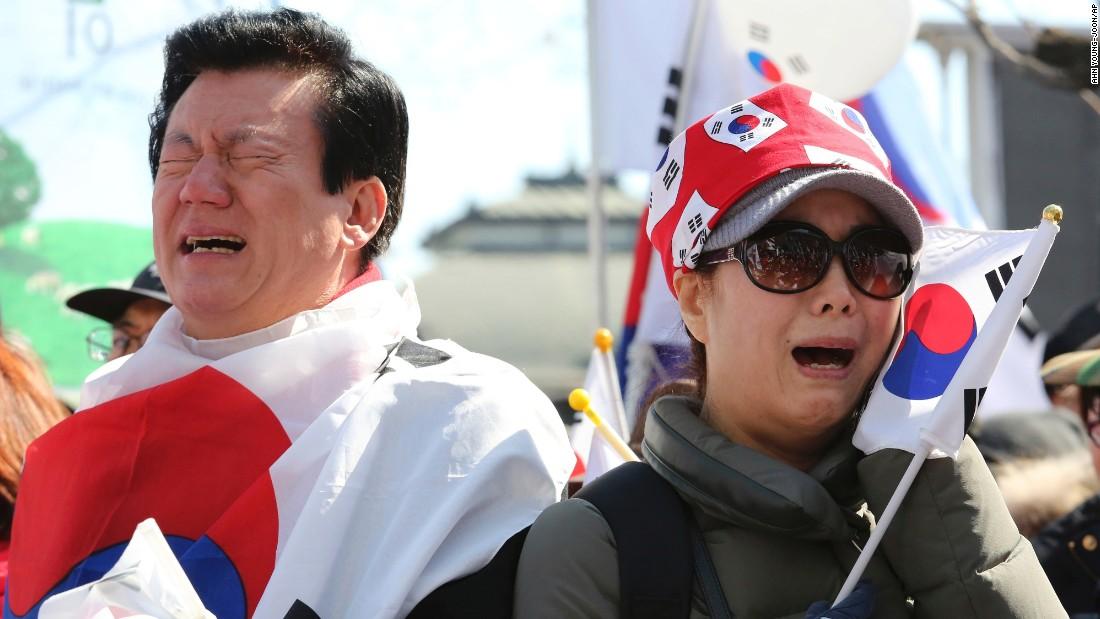 People opposing Park's impeachment cry during a rally near the Constitutional Court.