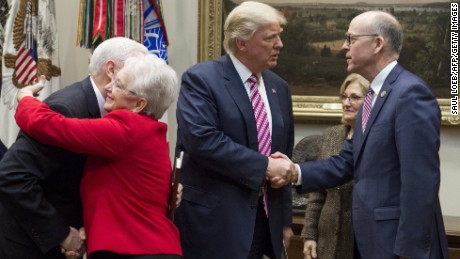 US President Donald Trump shakes hands with Representative Greg Walden (R), Republican of Washington and House Energy and Commerce Committee Chairman, alongside US Vice President Mike Pence (L), as he hugs Representative Virginia Foxx (2nd L), Republican of North Carolina and House Education and Workforce Committee Chairwoman, as they meet with House committee chairman about healthcare reform in the Roosevelt Room of the White House in Washington, DC, March 10, 2017.