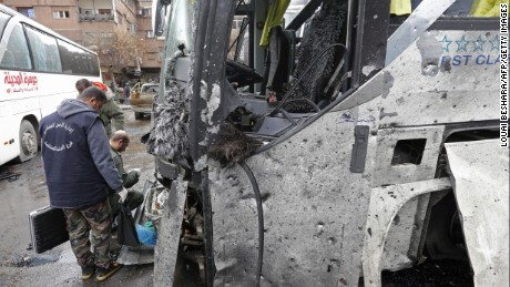 Syrian forensics examine a bus after the blasts.