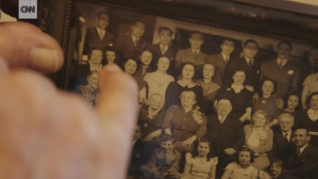 Millard Braunstein points out family members buried at Mt. Carmel Cemetery in a family photo.