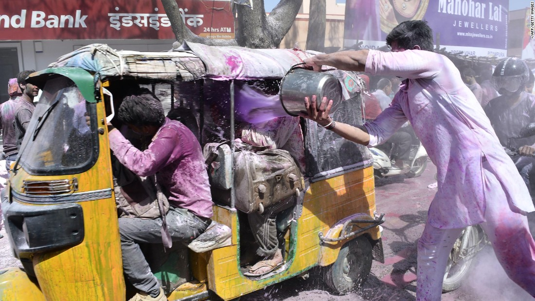 A man celebrating Holi dumps a bucket of colored water onto people in Mathura, India, on Monday, March 13.