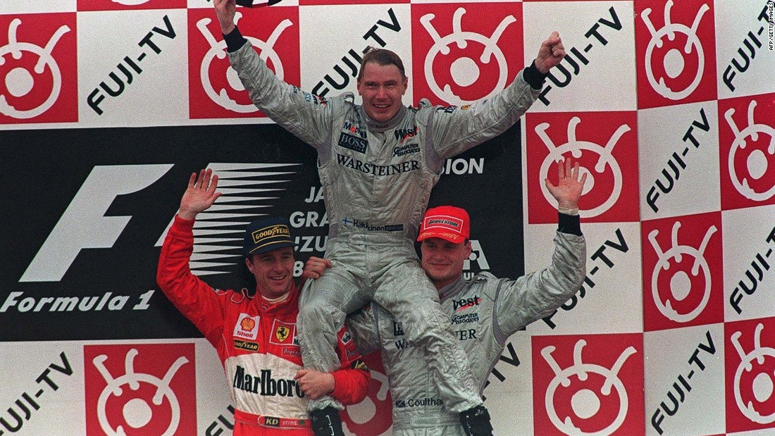 Hakkinen sits on the shoulders of Eddie Irvine (left) and his McLaren Mercedes teammate David Coulthard at the Suzuka race track in 1998 -- the year he won his first drivers title.
