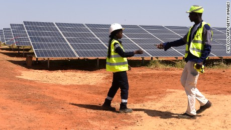 Technicians walk through solar panels on October 22, 2016 during the opening ceremony of a new photovoltaic energy production site in Bokhol. Senegal put into service one of sub-Saharan Africa's largest solar energy projects Saturday as it pushes to become a regional player in renewables on a continent where the majority remain off-grid. / AFP / SEYLLOU        (Photo credit should read SEYLLOU/AFP/Getty Images)