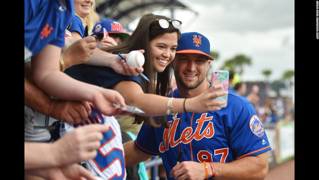 Former football star Tim Tebow, who is now a minor-league baseball player, poses with a fan before a spring-training game in Port St. Lucie, Florida, on Wednesday, March 8.