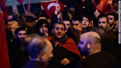 People gesture and wave flags as Turkish residents of the Netherlands gather for a protest outside Turkey's consulate in Rotterdam on March 11, 2017.  Protests erupted in the Dutch port city of Rotterdam late on March 11 outside the Turkish consulate amid a row with Ankara after Dutch authorities banned the visits of Turkish ministers. About 1,000 people waving Turkish flags gathered on the street leading to the consulate, as tensions rocketed over rallies abroad to help Ankara gain backing for an April referendum vote.  / AFP PHOTO / Emmanuel DUNAND        (Photo credit should read EMMANUEL DUNAND/AFP/Getty Images)