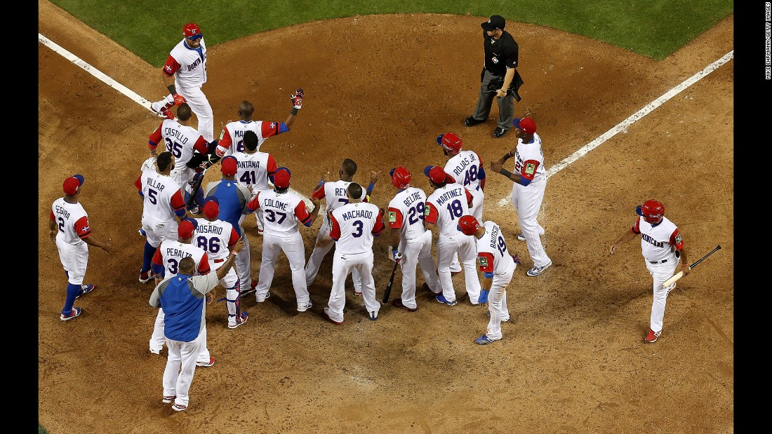 Nelson Cruz is congratulated by his Dominican teammates after he hit a three-run home run against the United States on Saturday, March 11. Both teams advanced to the next round of the World Baseball Classic.<br />