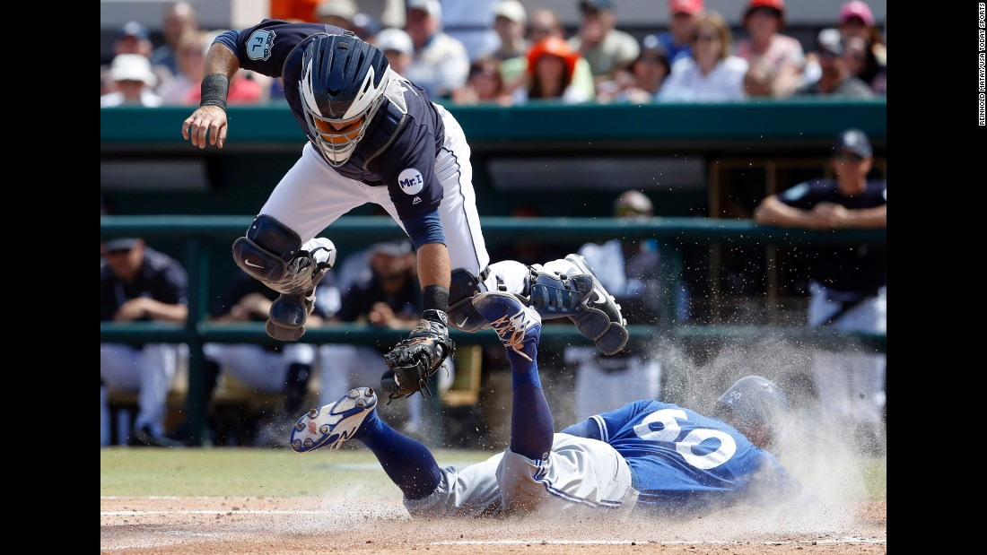 Toronto's Jon Berti slides safely under Detroit catcher Alex Avila during a spring-training game in Lakeland, Florida, on Friday, March 10.<br />