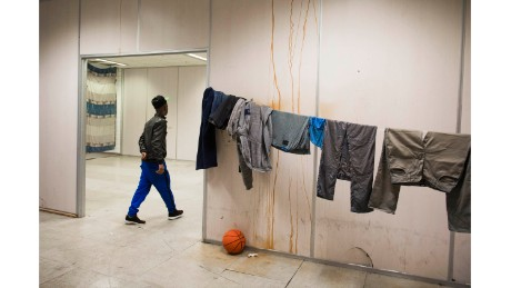 "A refugee passes drying laundry at the group's Vluchttoren location in 2015. Many of the buildings squatted are given a name beginning with ""vlucht"" meaning ""flight,"" a moniker for refugees in Dutch."