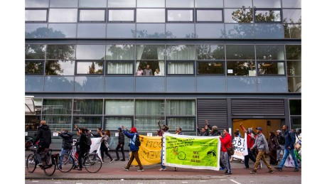 On the day they are evicted from the Vluchtgebouw, We Are Here members march through Amsterdam to demonstrate against the treatment of asylum-seekers. Their banner depicts Dutch PM Mark Rutte saying 'I don't respect human dignity.'
