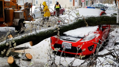Workers clear debris Tuesday after a tree branch fell on a parked car in Baltimore.