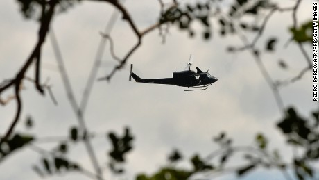 A Huey UH-1 Mexican army helicopter overflies the area on September 7, 2016 in El Chauz, Michoacan State, Mexico, near the place where a police helicopter participating in an operation to capture leaders of an unidentified criminal group was shot down on the eve. Authorities hunted on Wednesday for gang suspects who shot down a helicopter carrying police in western Mexico, killing four aboard in a clash highlighting the government's struggle to quell violence in the region. / AFP / Pedro Pardo        (Photo credit should read PEDRO PARDO/AFP/Getty Images)