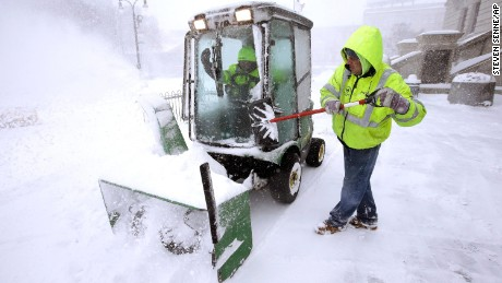 Public Works & Parks Department worker Jason Roy clears the windshield of a small plow being used to clear snow at City Hall in Worcester, Massachusetts, on March 14.