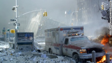 An ambulance, covered with debris, is on fire after the collapse of the first World Trade Center Tower 11 September, 2001 in New York. Two hijacked passenger planes were crashed against the twin towers causing the collapsed of both buildings. AFP PHOTO  Doug KANTER (Photo credit should read DOUG KANTER/AFP/Getty Images)
