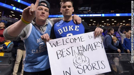 A fan of the North Carolina Tar Heels and the Duke Blue Devils pose for a photo while holding a sign referring to the Duke/UNC rivalry during the ACC Basketball Tournament at Barclays Center on Friday.
