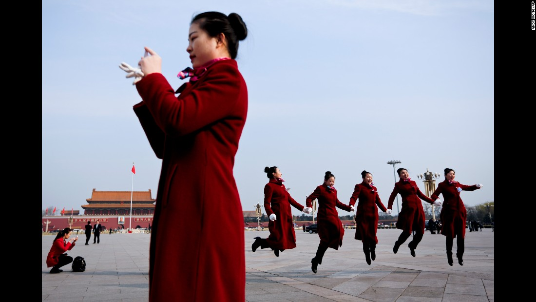 Hospitality staff members jump for a photo at Beijing's Tiananmen Square on Wednesday, March 15. Beijing was hosting the closing session of the National People's Congress.