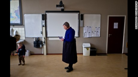 An elderly woman waits her turn to receive her ballot prior to casting her vote for Dutch general elections at a polling station set up in a school in Staphorst, Netherlands, Wednesday, March 15, 2017. Amid unprecedented international attention, the Dutch go to the polls Wednesday in a parliamentary election that is seen as a bellwether for the future of populism in a year of crucial votes in Europe. (AP Photo/Muhammed Muheisen)