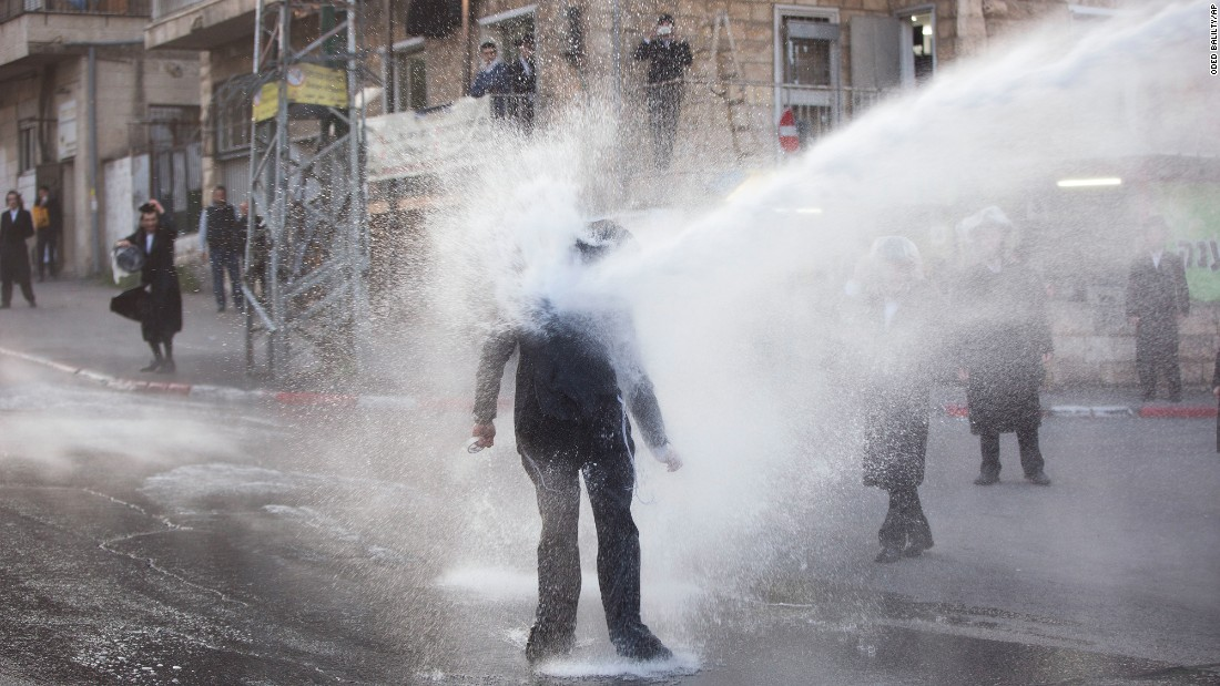 An ultra-Orthodox Jew is hit by a police water cannon during an anti-draft protest in Jerusalem on Wednesday, March 15.