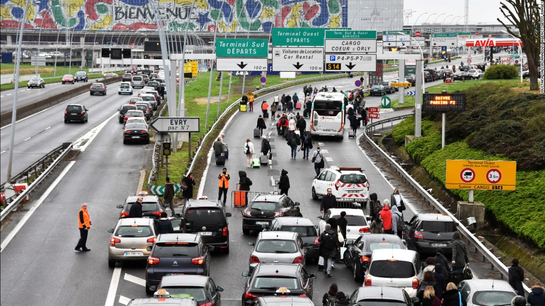 Passengers evacuated from Orly airport walk on the highway.