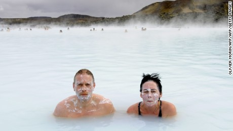 Tourists stand in the Blue Lagoon outside Reykjavik on 26 April, 2009. The Blue Lagoon's blue and green waters come from natural hot water springs flowing through rocks of lava. The  lagoon might have some health properties. AFP PHOTO OLIVIER MORIN. (Photo credit should read OLIVIER MORIN/AFP/Getty Images)